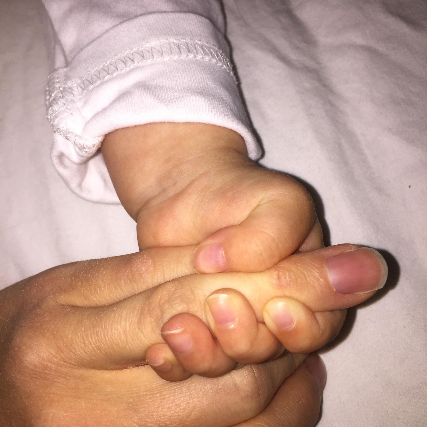 Nærbilde av liten hånd som holder hardt rund to fingre