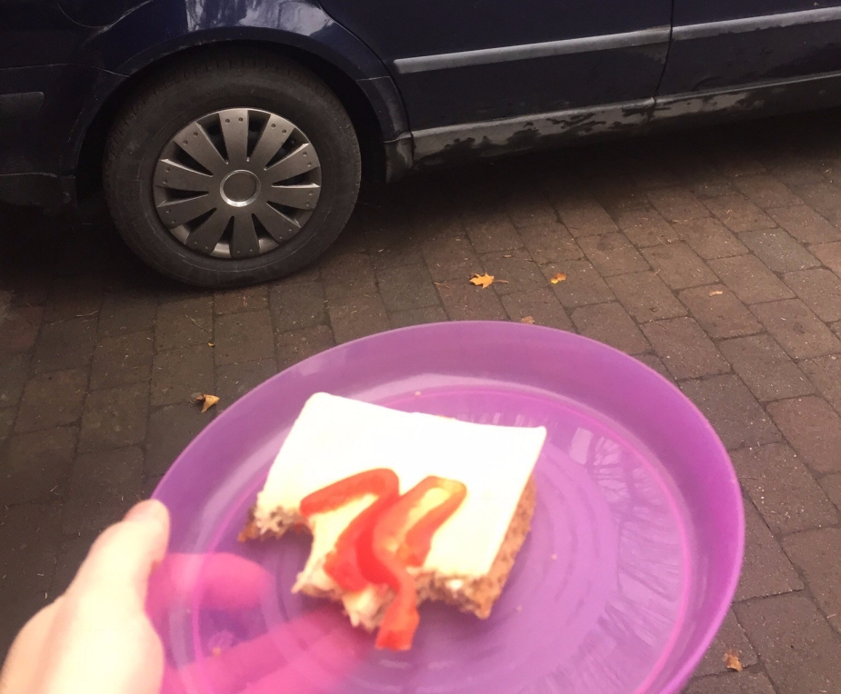 Fat med en halvspist brødskive med en bil i bakgrunnen