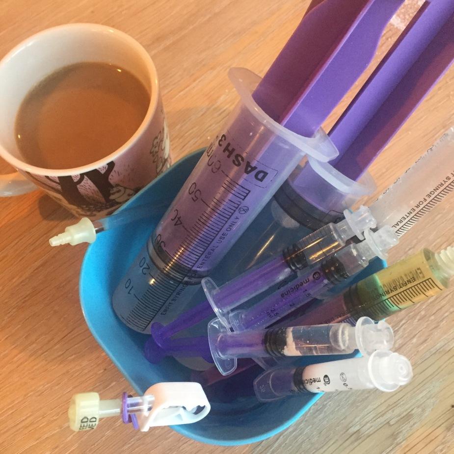 En kaffekopp og en plastboks med medisinsprøyter