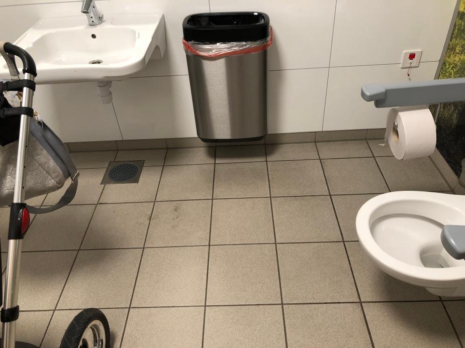 Bilde av gulvet på et handicaptoalett. Gulvet er møkkete, og det er trangt med plass mellom toalett og vogn.